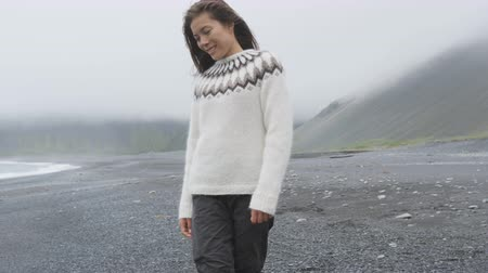 shy girl : Cute beautiful woman walking on black sand beach on Iceland wearing Icelandic sweater. Pretty multiracial Asian  Caucasian female model looking shy down by the ocean sea smiling happy. 90 FPS Stock Footage