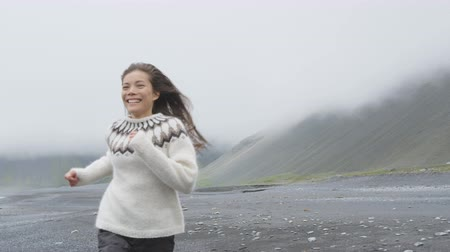 pulóver : Cheerful happy woman having fun running on Iceland beach laughing joyful and playful wearing Icelandic sweater on black sand beach. Female model girl enjoying nature landscape at ocean sea. RED EPIC.
