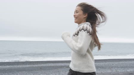 pulóver : Happy woman having fun running on Iceland beach laughing joyful and playful wearing Icelandic sweater on black sand beach. Female model girl enjoying nature landscape at ocean sea. RED EPIC 90 FPS.