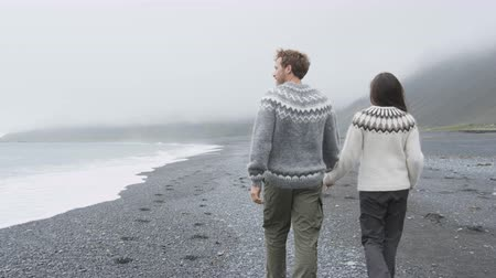 amantes : Couple walking on beach holding hands on Iceland. Romantic couple walking wearing Icelandic sweater on black sand beach from behind showing rear view of back. Tracking steadicam with RED EPIC 60 FPS.