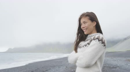 pulóver : Beautiful woman walking on black sand beach on Iceland wearing Icelandic sweater. Pretty multiracial female model looking pensive at ocean sea smiling happy. RED EPIC  90 FPS.