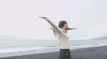 pulóver : Happy free woman on Iceland in Icelandic sweater on black sand beach. Joyful girl happy swirling around smiling outdoors in nature laughing having fun. Asian Caucasian female model. RED EPIC 90 FPS.