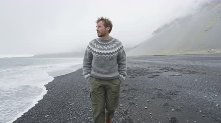 gündelik kıyafetler : Handsome man walking black sand beach on Iceland wearing Icelandic sweater. Good looking male model looking pensive at ocean sea. RED EPIC FOOTAGE. Stok Video