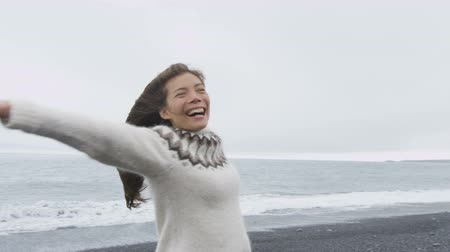 pulóver : Dancing free happy woman on Iceland dancing of joy in Icelandic sweater on black sand beach. Joyful girl happy swirling around smiling outdoors in nature laughing having fun. RED EPIC 90 FPS. Stock mozgókép