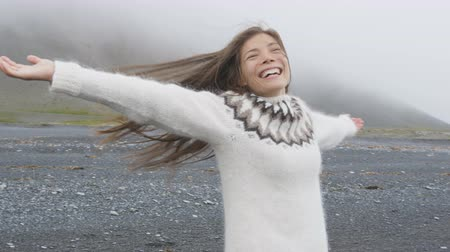 tourism : Freedom - happy woman on Iceland dancing of joy in Icelandic sweater on black sand beach. Joyful girl happy swirling around smiling outdoors in nature laughing having fun. RED EPIC 90 FPS SLOW MOTION.