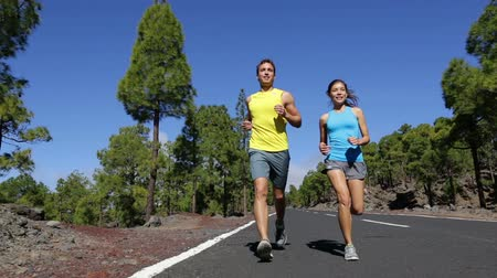 kimerül : Running couple exercising living healthy lifestyle talking starting jogging on mountain forest road. Sport runners on run outdoors working out. Fit young fitness model man and asian woman outside