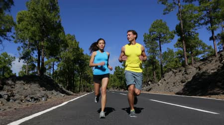 kimerül : Running runner man and woman jogging training on mountain road.  Fitness runners working out for marathon on forest road in amazing nature landscape. Two models exercising.