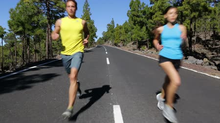 jogging : Sport fitness running people jogging outdoors on mountain road. Male and female fitness model working out training for marathon run in nature landscape. Two young runners exercising outside.