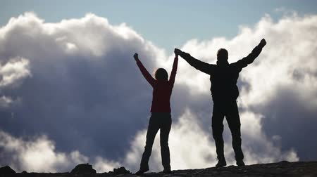 dosažení : Achievement, Success and accomplishment high five concept with hiking people cheering and celebrating of joy with arms raised outstretched up above the clouds on trekking hike. Woman and man Hikers. Dostupné videozáznamy