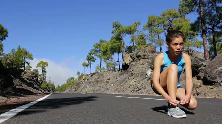 calçados : Young woman tying running shoes before run. Female runner going jogging training outdoors on summer day on mountain forest road. Asian Caucasian athlete sport model. Stock Footage