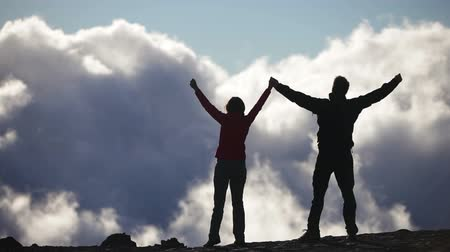 dosažení : Success, achievement and accomplishment concept with hiking people cheering and celebrating of joy with arms raised outstretched up above the clouds on trekking hike. Woman and man Hikers outside.