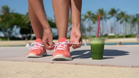 calçados : Running woman runner with green vegetable smoothie. Fitness and healthy lifestyle concept with female model tying running shoe laces. Stock Footage