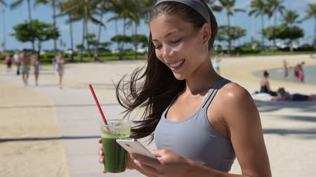 az egészséges életmód : Smartphone fitness woman drinking green vegetable smoothie juice using smart phone app after running workout training. Fit mixed race female girl living healthy wellness lifestyle on summer beach.