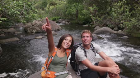 aktywność : Hiking people in outdoor activity wearing backpacks relaxing. Hikers  woman and man hiker looking with smiling happy. Healthy lifestyle image from Iao Valley State Park  Wailuku  Maui  Hawaii  USA.