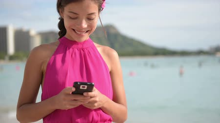 misturado : Smartphone woman using smart phone app on Waikiki Beach. Girl sms text messaging or browsing on internet smiling happy outdoors. Mixed race Asian Caucasian female model on Oahu  Hawaii  USA. Stock Footage