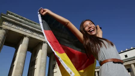 germania : Bandiera tedesca - donna felice a Berlino Brandenburger Tor tifo festeggiare sventolando bandiera da Berlino Germania Porta di Brandenburgo. Allegro eccitato donna multirazziale in Germania il concetto di viaggio.