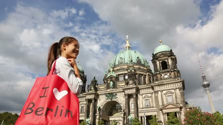 alışveriş : Tourist in Berlin  Germany on travel visiting landmarks. Woman with shopping bag saying I LOVE BERLIN smiling happy in front Berlin Cathedral  Berliner Dom and Fernsehturm  Berlin TV Tower.