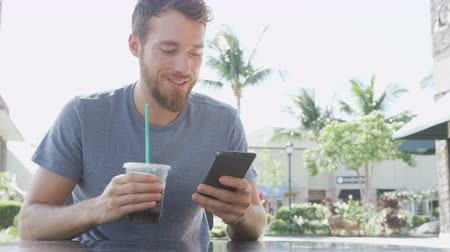 saman : Man on cafe using smart phone app text messaging sms drinking iced coffee in summer. Handsome young casual man using smartphone smiling happy sitting outdoors. Urban male in his 20s. Stok Video