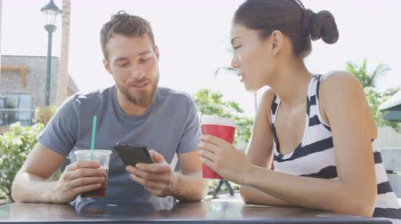 использование : Smart phone Cafe couple looking at smartphone screen app laughing having fun on date drinking coffee in summer. Young man using talking with Asian woman sitting outdoors. Friends in late 20s.