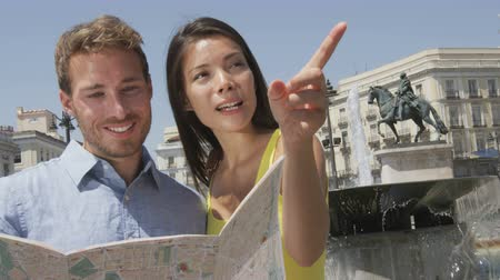 quadrado : Tourists couple with map in Madrid. Sightseeing people looking at map for tourist attractions and famous landmarks while visiting Puerta del Sol in Madrid, Spain. Multiracial couple.