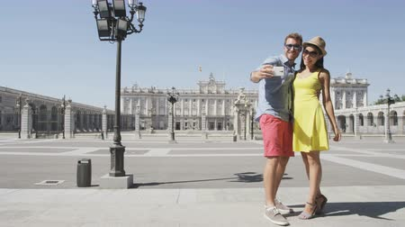 palacio real : Tourists couple taking selfie self portrait photograph using smart phone by Royal Palace of Madrid, Spain, People traveling visiting Spanish tourist attractions landmarks, Palacio Real de Madrid. Stock Footage