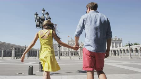 palacio real : Young couple walking holding hands happy and romantic in front of Royal Palace of Madrid, Spain, Tourists traveling in Europe visiting Spanish tourist attractions landmarks, Palacio Real de Madrid. Stock Footage