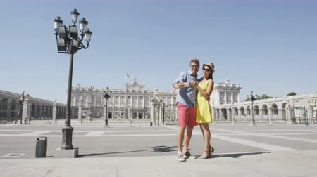 palacio real : Tourists travel couple taking selfie self portrait photograph using smart phone by Royal Palace of Madrid, Spain, People sightseeing Spanish tourist attractions landmarks, Palacio Real de Madrid.