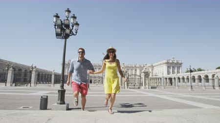 palacio real : Young couple walking holding hands happy and romantic in front of Royal Palace of Madrid, Spain. Tourists walking into church cathedral Almudena while traveling visiting Spanish tourist attractions. Stock Footage