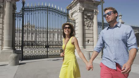 utazó : Young couple walking holding hands happy and romantic in front of Royal Palace of Madrid, Spain, Tourists traveling in Europe visiting Spanish tourist attractions landmarks, Palacio Real de Madrid. Stock mozgókép