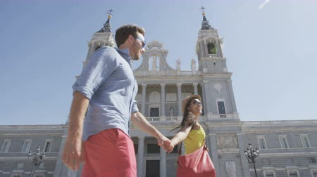 madryt : Couple holding walking hands in Madrid, Spain in front of landmark and tourist attraction Almudena Cathedral.