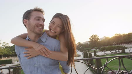 кавказский : Romantic couple embracing in love laughing having fun. Multicultural man and woman smiling happy in el Retiro in Madrid, Spain, Europe. Asian girl, young Caucasian man. RED EPIC SLOW MOTION.