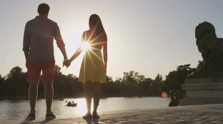 madryt : Romantic Madrid couple holding hands at sunset in city park el Retiro, Madrid, Spain. Happy couple enjoying sunlight at park lake. Young woman and man relaxing. Wideo
