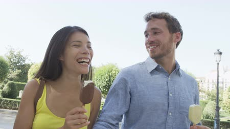 bengala : Couple eating ice cream bar on stick laughing having fun outside in city park. Young urban multiracial couple, Asian woman, Caucasian man.