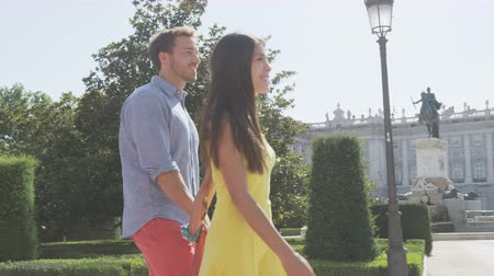 palacio real : Couple holding hands walking romantic on city park square in Madrid, Plaza de Oriente, Famous landmark in Madrid, Spain with the Royal Palace in background. RED EPIC SLOW MOTION.