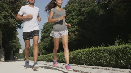 madryt : Runners running couple jogging in city park. Exercising woman and man runner training together on run living healthy active lifestyle in Buen Retiro Park, Parque el Retiro in Madrid, Spain, Europe.