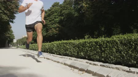 kimerül : Running man sprinting fast at speed with close up of running shoes.Male sprinter in city park, El Retiro Madrid, Spain. RED EPIC SLOW MOTION.