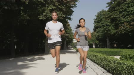 estilo de vida saudável : Running couple runners jogging in city park. Exercising woman and man runner training together on run living healthy active lifestyle in Buen Retiro Park, Parque el Retiro in Madrid, Spain, Europe.