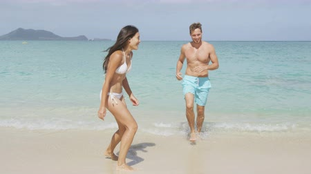 outdoor : Happy couple having fun on beach vacation during summer holiday. Multiracial couple running out of water laughing in the sun. Young adults carefree relaxing sitting down in sand. Lanikai, Oahu, Hawaii