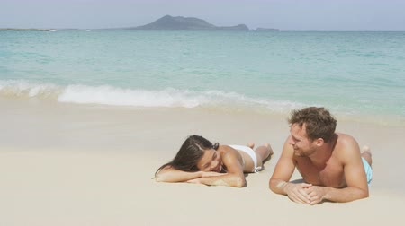 медовый месяц : Couple in love relaxing on beach during vacation travel. Happy woman and man on honeymoon sun tanning lying on the sand having fun in on Lanikai beach, Hawaii, USA.  SLOW MOTION.