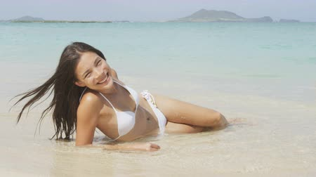 lefekvés : Beach girl in bikini lying on sand in turquoise water in tropical paradise. Sexy happy smiling woman in relaxing in the sun tanning. Beautiful mixed race Asian Caucasian model. Lanikai, Oahu, Hawaii.