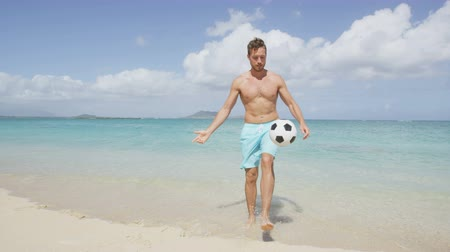 muži : Beach fun - man beach playing football juggling soccer ball having fun living healthy active lifestyle during summer travel vacation holidays on beautiful tropical beach. Dostupné videozáznamy