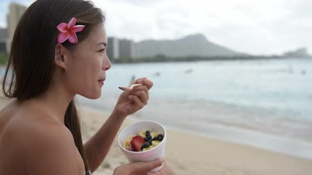 spoons : Acai bowl - woman eating healthy food on beach. Girl enjoy acai bowls made from acai berries and fruits outdoors on beach for breakfast. Girl on Hawaii eating local Hawaiian dish.