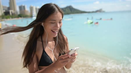 sluch : Music on earphones from smartphone. Woman on beach listening to music on smart phone walking in bikini happy dancing. Beautiful mixed race Asian Caucasian girl on Waikiki Beach, Oahu, Hawaii, USA. Dostupné videozáznamy
