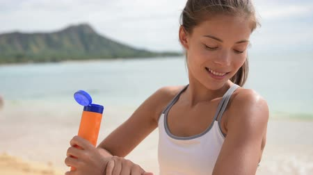pleťová voda : Fitness woman applying sunscreen suntan lotion using bottle outside on beach. Sporty Beautiful happy Asian girl with suntan cream using sun protection before running in Waikiki, Oahu, Hawaii, USA.