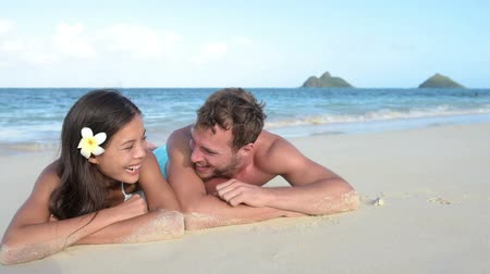 relação : Couple in love relaxing on beach during vacation travel. Happy couple portrait talking together in a relationship sun tanning lying on the sand having fun in on Lanikai beach, Hawaii, United States.