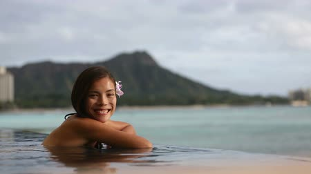 happy holidays : Vacation woman swimming at infinity pool on Hawaii smiling looking at camera. Beautiful asian young female adult enjoying happy holiday travel at Waikiki beach in Honolulu, Oahu, Hawaii, USA.