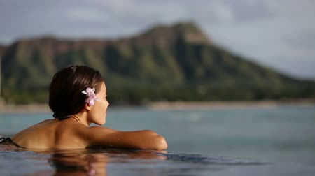 utazó : Holiday woman swimming at beach on Hawaii travel. Asian chinese young lady relaxing in infinity pool in luxury hotel resort on Waikiki beach in Honolulu, Oahu, Hawaii, USA.