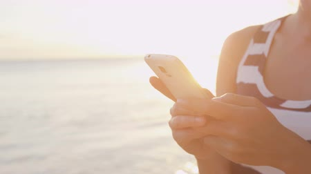 мобильный телефон : Woman sms texting using app on smart phone at beach sunset. Closeup of hands using smartphone outdoors. Sunshine and flare at ocean beach. Mobile cell phone close up. Стоковые видеозаписи
