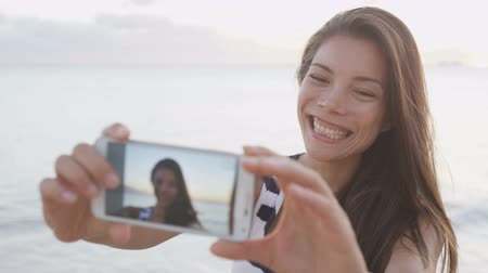 tourism : Girl taking selfie of herself using smartphone having fun outside on beach. Smart phone screen showing as woman takes selfies self portrait photos outdoors at beach sunset. RED EPIC SLOW MOTION.