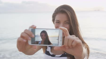 фотографий : Woman taking selfie using smartphone having fun outside on beach. Smart phone screen showing as girl takes selfies self portrait photos outdoors at beach sunset. RED EPIC SLOW MOTION.